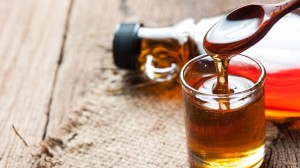 maple syrup in glass bottle on wooden table
